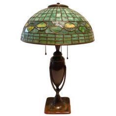 "USA Period: c. 1905 Description: Tiffany lamp with patinated bronze ""torpedo"" base with clasped acorn motif and 14"" diameter leaded stained ..."