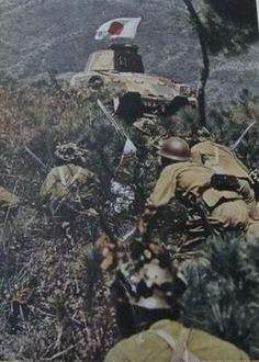Japanese army troops, supported by tanks, move through brush as they assault a Chinese position during an early morning attack