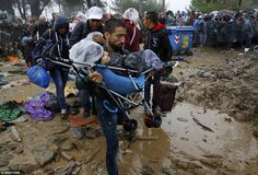 Desperate: A Syrian refugee walks through the mud carrying a child in a pram as he cross t...