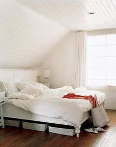 White bedroom with under-the-bed storage baskets