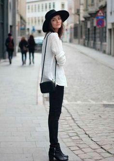 Mulher parada na calçada posa para foto usando calça jeans preta, bota preta, maxi tricot, bolsa preta a tiracolo e chapéu preto
