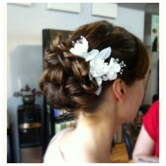 Elegant low bun with soft curls with a white flower. Beautiful and simple.  Bridal Hair by Karen Cole