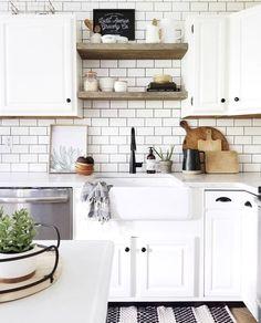Kitchen goals! Love the white cabinets, white subway tile backsplash, black + white rug and the splash of wood + greenery!