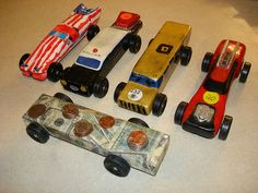 """Five pinewood derby cars from five years of Cub Scouts. This years """"car,"""" his last one ever, is in front.     We need money, or not! Check out:   http://www.reallyfastmakemoney.com"""