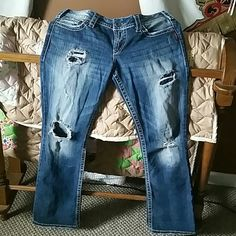 Silver jeans Low rise. Pioneer boot cut. Four holes in front with a worn look. Two top holes are covered from inside and two holes on the knees aren't. Some wear on bottom shown in pic. Size 30 regular. Price is firm but I offer discounts on bundles! Thanks for looking! :) Silver Jeans Jeans Boot Cut