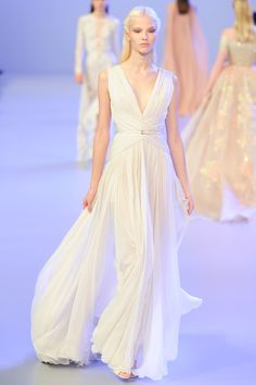 Brides: Wedding Dresses at Paris Haute Couture Fashion Week Elie Saab infused his collection with angelic pastels—blush, pale blue and lilac—and his classic floral-appliquéd dresses were back with delightful new embellishments (think cascading pearl embroidery) and styles; specifically, elegant and simple pleated Grecian gowns. The show-closing wedding dress was featured cascading embroidery falling on a grand blush colored ball skirt.