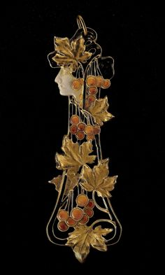 RENÉ LALIQUE |   Gold and Enamel 'Autumn' Pendant. Circa 1898-1900. Of openwork design depicting a female head in profile applied with matte gray/green enamel to symbolize the dying year, her hair in brown enamel entwined with branches of cascading leaves in gold and autumnal fruits of fiery orange enamel, and pale creamy pink contre émail.