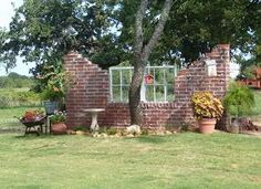 This idea was submitted by Tx-Girl. She built a mock wall out of leftover bricks, placed an old window in it and added decorations, to make an outdoor room, and divide her yard from the field beyond.