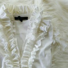 ✨HP✨  BCBGMAXazria ruffle collar blouse Beautiful white ruffle collar blouse. Side zipper. Gold buttons at cuffs and larger than life ruffles around collar. Wore a few times and the only issue is there is some kind of scuffing on the back shoulder and part of ruffle. Shown in 4th pic. 68% cotton 28% nylon 4% spandex. BCBGMaxAzria Tops Blouses