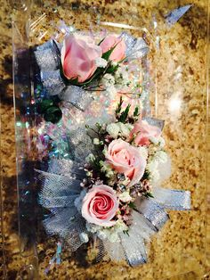 Fresh mini pink roses with baby's breath and wax flower. Silver tulle, silver ribbon, clear jewels. Wrist corsage and Boutineer for prom!