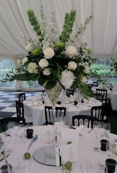 "COLORS ONLY Wedding Flowers ""Breathtaking white wedding flowers for your wedding reception. This fabulous wedding centrepiece uses a Martini vase lined with fresh cut limes, dramatic lime green Bells of Ireland and ivory delphiniums,  white and greeney white hydrangeas, ivory Avalanche roses, spider green Anastasia chrysanthemums, ivory scented stocks and Ammi.  Cut limes as place card holders and potted fresh herb favours on the tables complete the look."""