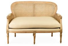 Classic 18th century French revival style maintains an approachable elegance with this light and airy cane-backed sofa.