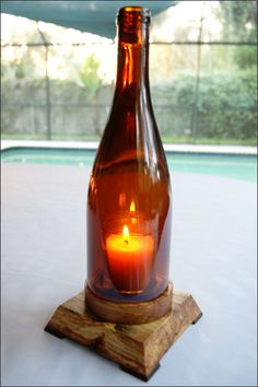 """Wooden Stand 1 Wine Bottle Candleholder - The color of the glass adds an ambiance great for an indoor table centerpiece, mantel display, wine bar, or a patio or porch area. The bottle sits on a 3/4 """" (+/-) wood base with wooden feet. Each bottle fits into its own individual stand."""
