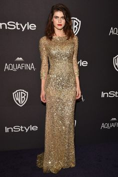 Alexandra Daddario wears a gold sequin gown by Reem Acra with Paul Andrew shoes