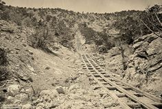 Early rails: A wooden balanced incline used for gold mining, at the Illinois Mine in the Pahranagat Mining District, Nevada in 1871. An ore car would ride on parallel tracks connected to a pulley wheel at the top of tracks