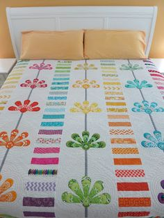 The bright, cheerful colors in this quilt pop against the white background.