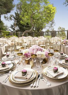 Beautiful décor at the reception, including mixed metallic vases, lush pink flowers, and gilded china, tied everything together.