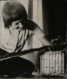 Girl tickling cat's nose with feather... undated but I'd guess c. 1920s, from the hair. Source