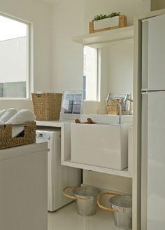 O branco e a cor das fibras naturais iluminam a área de serviço, idealizada pela arquiteta Débora Aguiar.