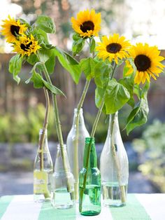 Individual sunflowers make a simple summer centerpiece. Find more beautiful centerpieces: www.bhg.com/party/birthday/themes/pretty-outdoor-centerpieces-and-table-accents/?socsrc=bhgpin062712