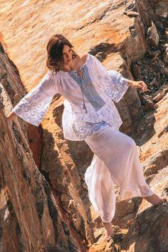 Blusa de silueta holgada, escote Bardot, bajo y mangas acampanadas y detalles bordados en contraste.