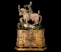 Wykonana pomiędzy 1590 a1597 rokiem figurka, na którejśw. Jerzy szykuje się dozadania śmiertelnego ciosu smokowi. Głownia miecza została wykonana zkryształu górskiego, natomiast samą statuetkę zrobiono zezłota, częściowo odlewanego, aczęściowo repusowanego. Całość bogato ozdobiono wielobarwną emalią orazkamieniami szlachetnymi, takimi jak rubiny, szmaragdy iperły. Końzostał wyrzeźbiony zagatu ichalcedonu. Cokół figury zdobi herb bawarski.