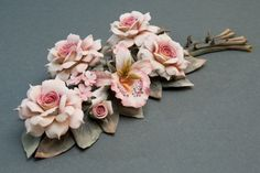 Elegant and refined branch of roses and orchids in Capodimonte porcelain finely worked with each flower entirely worked by hand and laid on a sophisticated branch composed of leaves and branches, also entirely handmade by the artist.             Dimensions cm. 10x40