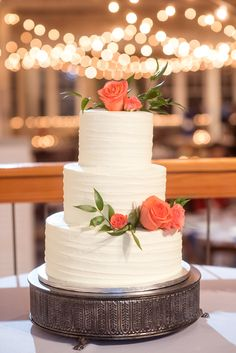 Mikkel Paige Photography photos from a wedding reception at The Stockroom at 230 in Raleigh. A picture of the white tiered buttercream cake adorned with coral roses.