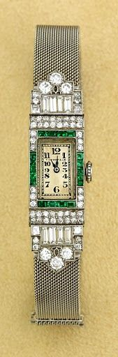 Circa 1933 Tiffany wristwatch: diamonds, emeralds, and set in platinum with platinum mesh band.