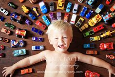 three year old smiling with his cars