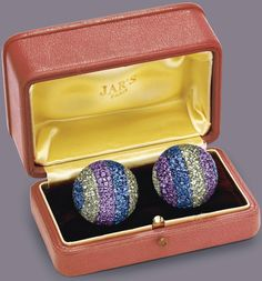 """A PAIR OF DIAMOND AND MULTI-COLORED SAPPHIRE """"BALL"""" EAR CLIPS, BY JAR. Each of bombé design, pavé-set with blue, green and violet sapphires, enhanced by a line of circular-cut diamonds, mounted in 18k gold and silver, with French assay marks and maker's marks, in a JAR pink leather box. Signed JAR, Paris (2). Price Realized $602,500 / Estimate $100,000 - $150,000 [C. NY - THE COLLECTION OF ELIZABETH TAYLOR: THE LEGENDARY JEWELS, EVENING SALE (I) - 13 DEC. 2011] #JARParis #JoelArthurRosenthal"""