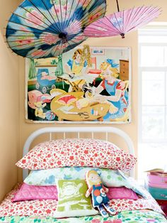 Antique paper parasols and a 1950s home-ec poster decorate this little girl's room. #decorating #kids