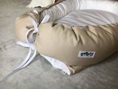 Kokon niemowlęcy beżowy. Kokon przypomina rożek  otula niemowlę i ogranicza mu przestrzeń, co sprawia,że dziecko czuje się bezpiecznie, jak w brzuszku u mamy.  W ciągu dnia kokon niemowlęcy można wykorzystać wszędzie tam gdzie w danym momencie przebywamy, może posłużyć jako wkład do Kosza Mojżesza, łóżeczka czy wózka. Jest to również świetne rozwiązanie dla rodziców śpiących ze swoim maluszkiem.  Niemowlę może swobodnie układać w nim nóżki.
