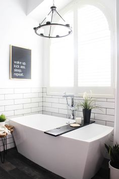 """Make your own custom typography canvas with iron-on vinyl and paint. A sleek modern canvas for your bedroom or bathroom. Love the """"wake up. kick ass. sleep. repeat."""" Art in a beautiful modern bathroom."""