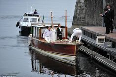 Arriving on the lake: The young couple are seen arriving at Borromeo castle by boat for their second wedding reception