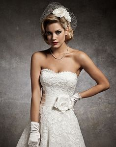Justin Alexander tea length wedding dress with strapless alancon sweetheart, silk dupion pleated cummerbund accented with silk flower and feather, circular cut lace tea length skirt.