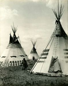A woman walking through a camp of the tribe of the blackfoot year 1913