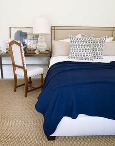 Nailheads add spark to an upholstered headboard in the guest room. Blue-and-white embroidered pillows by Dransfield & Ross. Blue cashmere throw by Hermès.   - HouseBeautiful.com