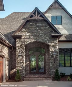Stone portico with timber wood detail! The Monarch Manor house plan 5040. #WeDesignDreams