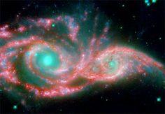 結合する銀河が描く天空の仮面 Photograph courtesy NASA/JPL-Caltech/STScI/Vassar 地球から1億4000万光年の位置にある2つの銀河が結合しようとしている様子を映し出したカラー処理画像。巨大な天空の仮面のように見える。目のように見える薄青色の部分は実際には各銀河の核であり、隈取りのような赤色部分は渦巻銀河の腕にあたる。NGC 2207とIC 2163と呼ばれるこの2つの銀河は、約4000万年前に互いの重力でダンスを踊り始め、最終的にいつかは1つに融合する。