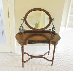 A wonderful Louis XVI styled vanity with tilting mirror. This very attractive piece is made of solid wood and select veneers. Appears to be walnut. The beveled glass mirror is in an oval frame atta...
