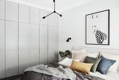 The norsuHOME - Main Bedroom Photographer: Lisa Cohen Stylist: Beck Simon  Paint: Dulux Terrace White Cabinetry: kaboodle Kitchens Carpet: Godfrey Hirst   Products:  Menu Franklin Pendant, Rubn Wall lights, Lola Donoghue Zebra Girl print, The Cullin Design Bedhead, norsu cushions, Honey Honey Creations knitted throw (all available at www.norsu.com.au)