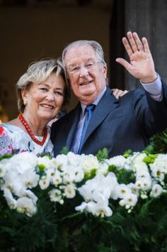 Belgium's King Albert II and Queen Paola wave to the crowd as they stand on the balcony of the City Hall in Liege, Belgium, during the last day of their 3-day farewell tour on Friday 19 July 2013