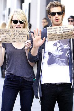 Andrew Garfield and Emma Stone use paparazzi for good, holding up signs directing their fans to check out two charities, www.gildasclubnyc.org and www.wwo.org, as they are spotted in NYC on September 15.