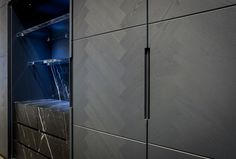 Piqu grey ash herringbone veneer, pocket doors conceal a full stone fronted set of drawers and work surface, UV bonded glass shelves.