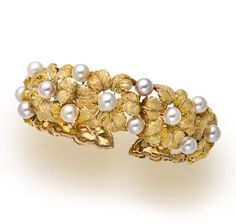 An eighteen karat gold and cultured pearl cuff bracelet, Buccellati of openwork textured foliate design, enhanced by cultured pearls, measuring approximately 6.00mm.; signed Buccellati, Italy, no. 12881; gross weight approximately: 48.1 grams; diameter: 2 1/4in.