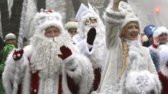 "Russia-People dressed as Father Frost, the equivalent of Santa Claus, and Snow Maiden greet passers-by during a New Year's parade in Bishkek, Russia. In Russia, New Year's celebrations are very important (sometimes more than Christmas). Father Frost brings presents to children. The traditional greeting on New Year's is ""S Novym Godom."""