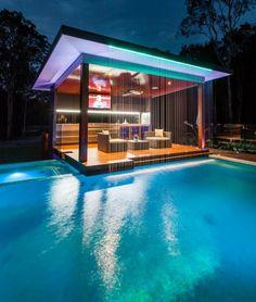 """pergola moderne, aménagée avec fauteuils en rotin, bar et écran plasma, """"flottante"""" dans la piscine moderne"""
