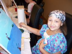Wigs 4 Kids recipient Elizabeth proudly displays her artwork created in our open studio art therapy classes.