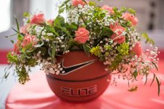 Basketball (Sports) Wedding Decorations - Husband and I were both college athletes and loved incorporating our life long passions in our best day ever. Coral roses and baby's breath inside the basketball.